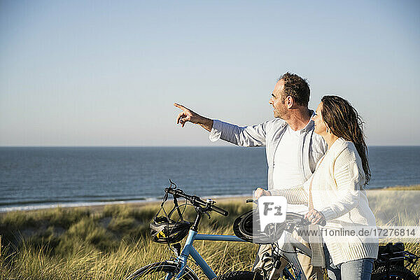 Happy couple with bicycles looking at view while standing on beach against clear sky