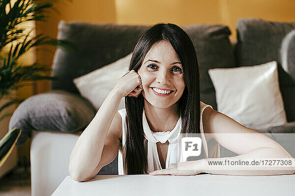 Smiling woman with hand on chin sitting at home