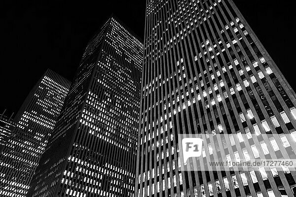 Illuminated modern buildings in downtown district at night  New York  USA