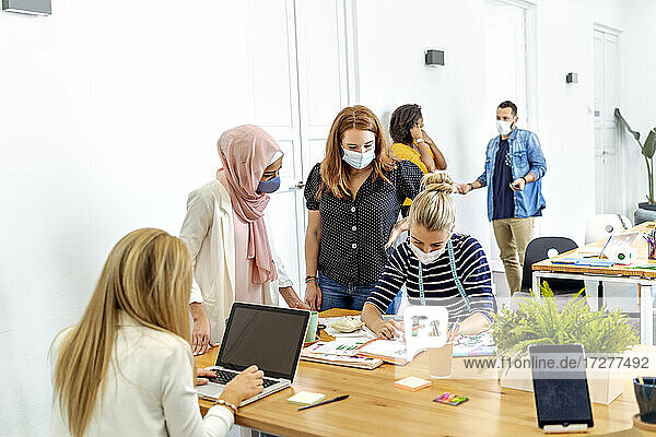 Women working while standing with coworker in background at office