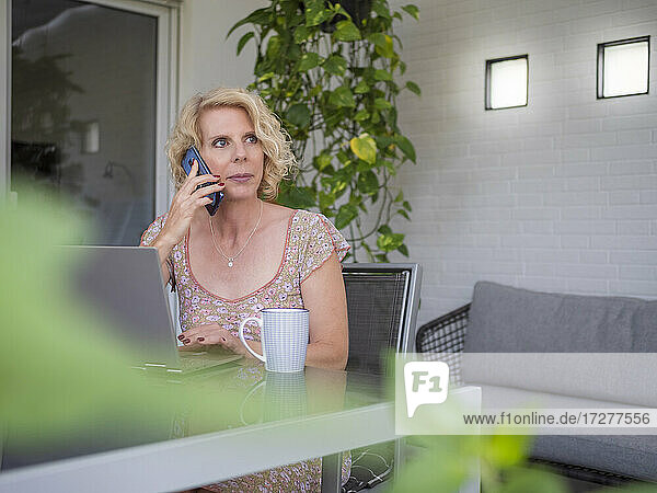 Thoughtful female professional talking on phone while sitting with laptop working at home