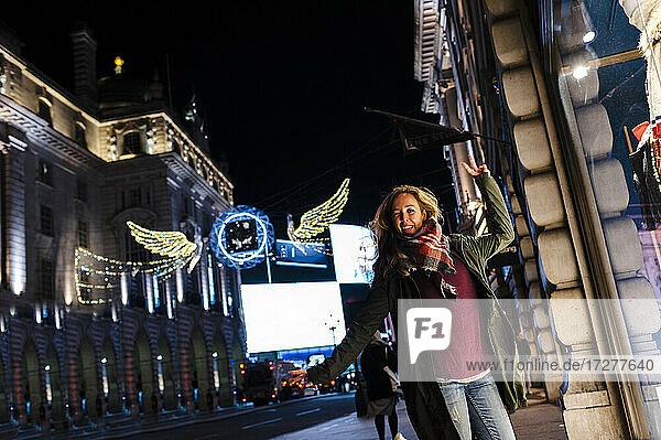 Carefree woman dancing while standing at Regent Street during Christmas in London  UK