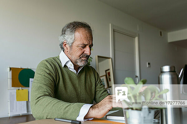 Mature man concentrating while working on laptop at home