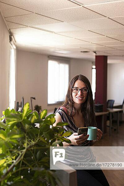 Smiling young female entrepreneur having coffee during office break