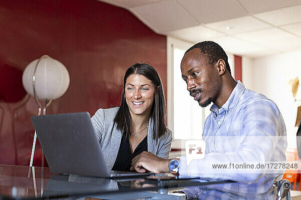 Multi-ethnic colleagues discussing over laptop in coworking office