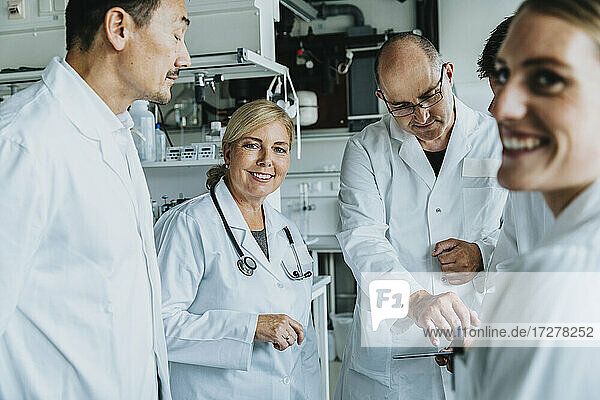 Smiling scientist working together with digital tablet while standing at laboratory