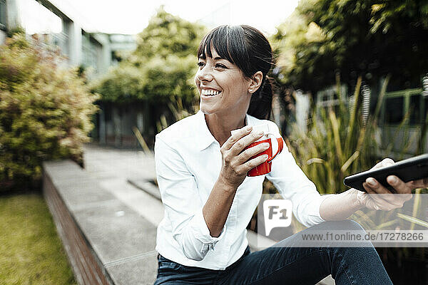 Lächelnde weibliche Fachkraft  die eine Kaffeetasse und ein Smartphone hält und wegschaut