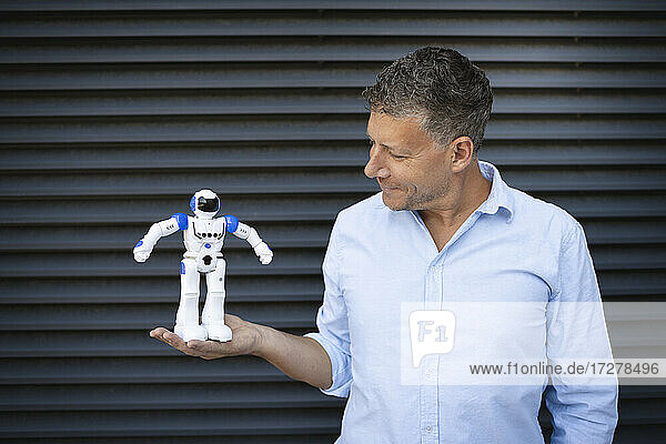 Businessman holding robot while standing against metal wall