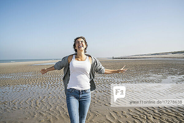 Cheerful young woman with arms outstretched walking at beach against clear sky