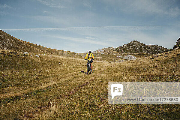 Female in warm clothing riding electric bicycle on mountain at Somiedo Natural Park  Spain
