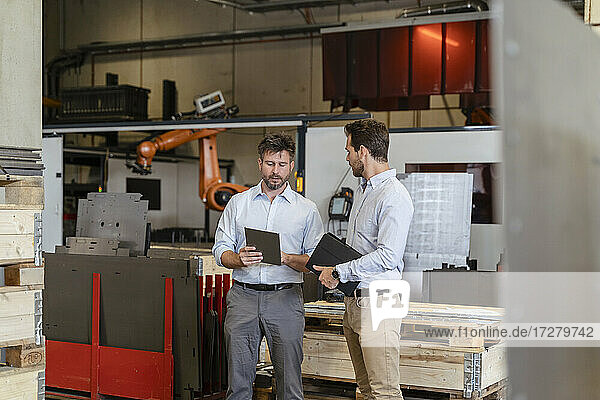Businessmen having discussion while using digital tablet at factory
