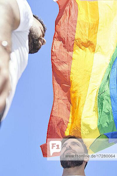 Gay couple with rainbow flag against clear sky during sunny day