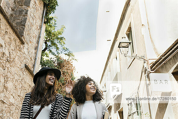 Smiling businesswomen walking in city during sunny day
