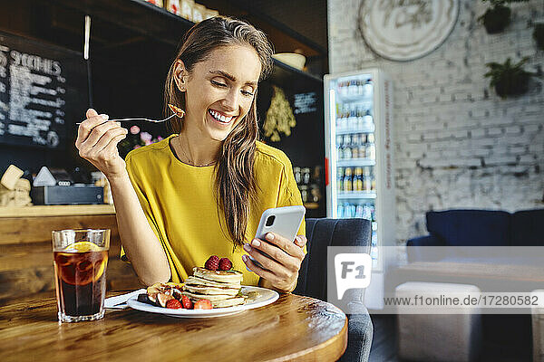 Smiling young female eating berry while using mobile phone at table in cafe