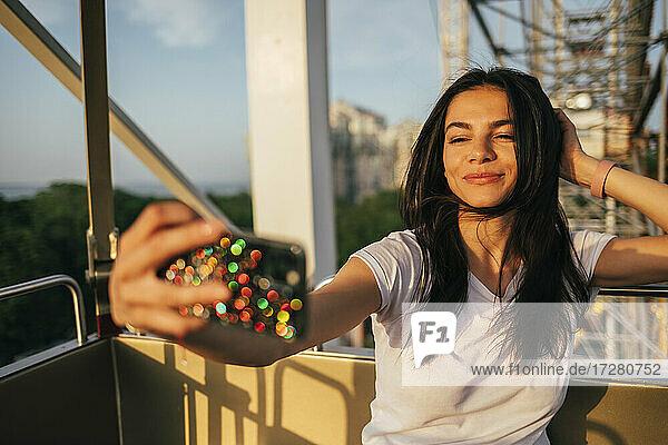 Beautiful woman taking selfie through mobile phone while enjoying on Ferris wheel ride