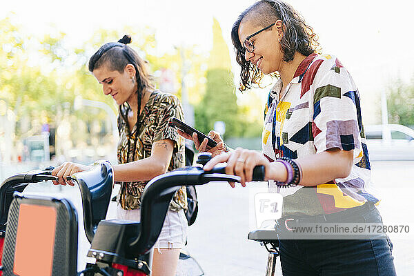 Lesbian couple using smart phone to unlock electric bicycle in city