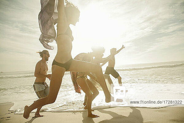 Cheerful friends jumping at beach on sunny day