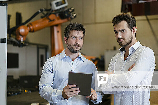 Confident businessmen using digital tablet while standing at factory