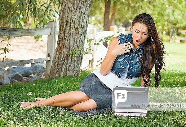Schockierte gemischtrassige junge Studentin mit Büchern mit Computer-Tablet draußen sitzen im Gras