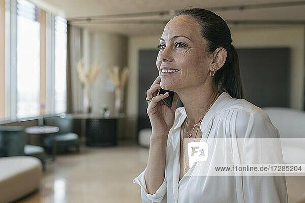 Lächelnde weibliche Fachkraft  die in der Lobby mit einem Mobiltelefon spricht