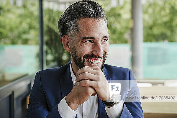Cheerful businessman with hand on chin looking away at cafeteria