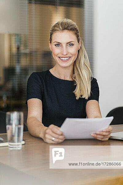 Schöne lächelnde Unternehmerin mit Dokument sitzt am Schreibtisch im Büro