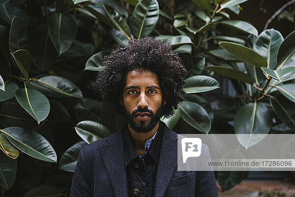 Fashionable man standing in front of plants
