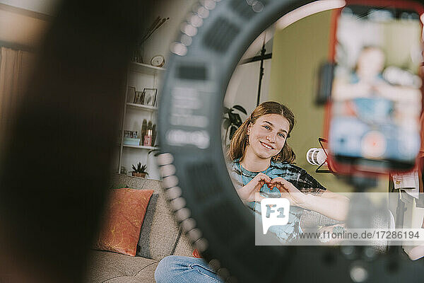 Smiling teenage girl making heart gesture while filming at home