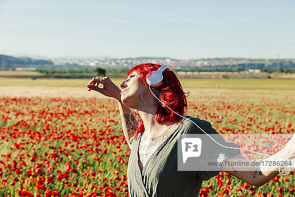 Carefree hipster woman dancing on poppy field