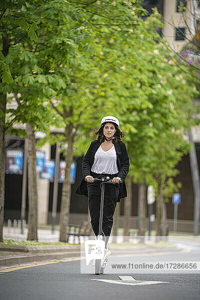 Young businesswoman riding electric push scooter on road