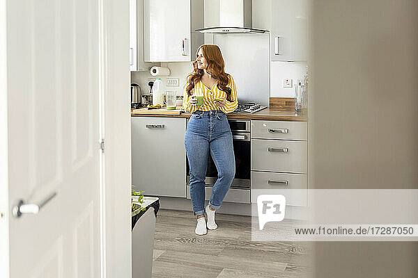 Redhead woman with healthy milkshake glass standing in kitchen while looking away