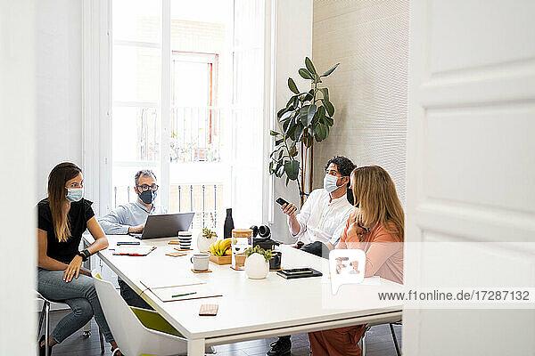 Männliche und weibliche Fachkräfte sitzen während der COVID-19 an einem Tisch im Coworking-Büro