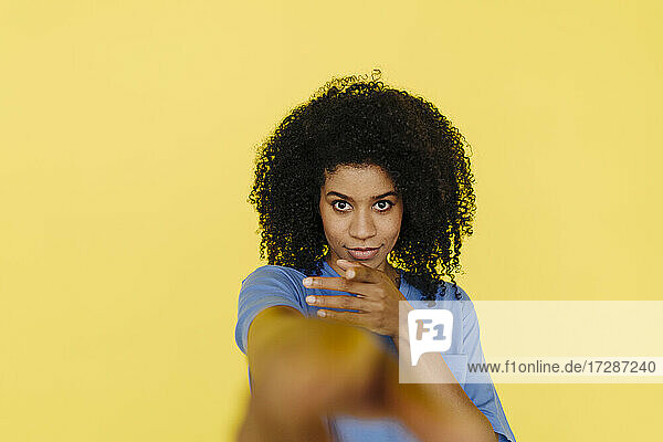 Afro woman gesturing in front of yellow background