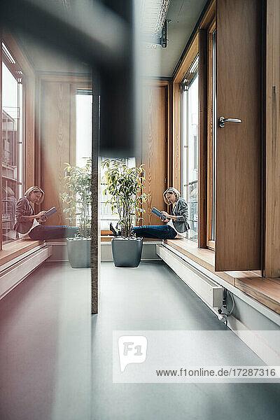 Unternehmerin  die ein digitales Tablet benutzt  während sie auf der Fensterbank im Büro sitzt