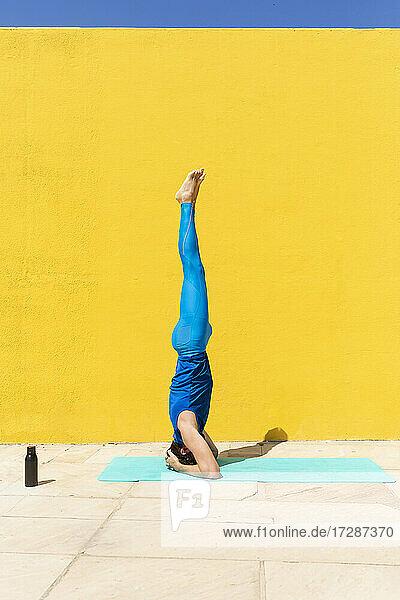 Mid adult man practicing Salamba Shirshasana by yellow wall during sunny day