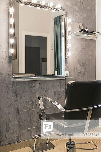 Illuminated light bulbs on mirror by chair at hair salon