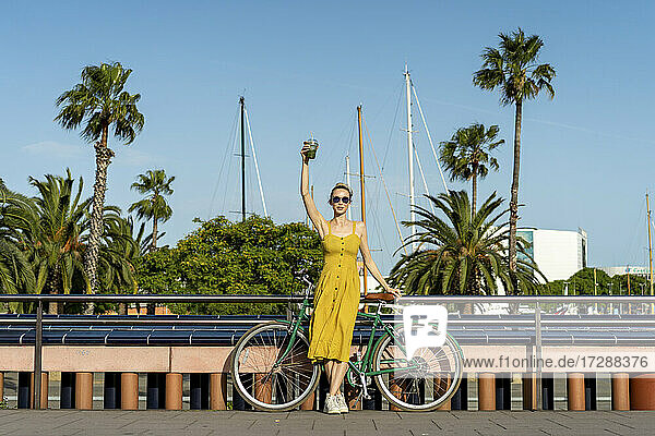 Young woman holding smoothie while standing with bicycle in city