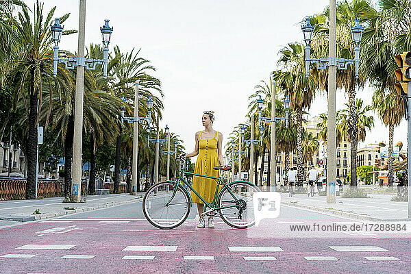 Woman looking away while standing with bicycle on road in city