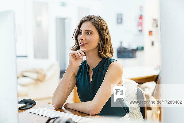 Junge Unternehmerin sitzend mit Hand am Kinn bei der Arbeit im Büro