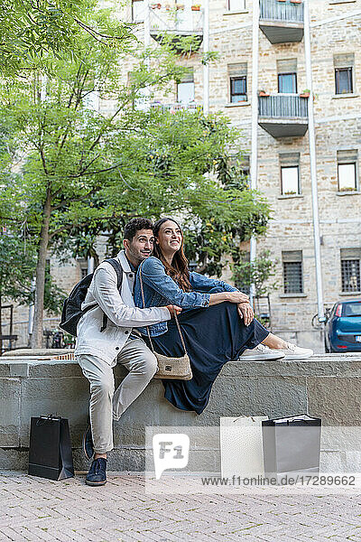 Couple looking away while sitting by shopping bags in city