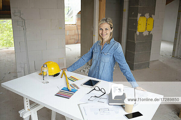 Smiling female building contractor standing at table in apartment