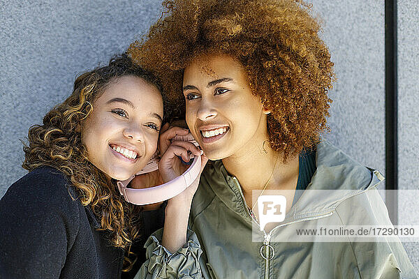 Smiling female friends listening music through headphones together