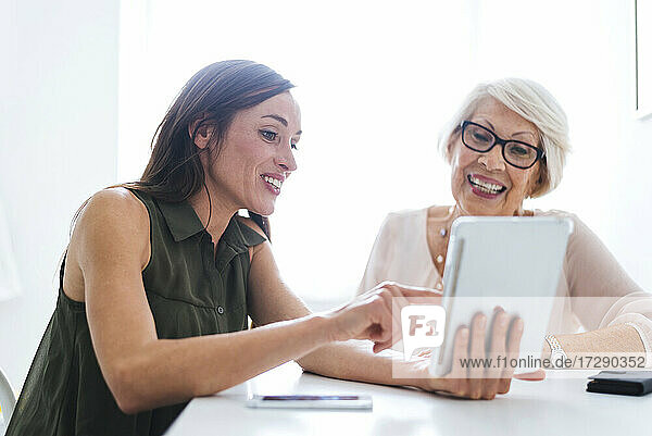 Smiling woman showing digital tablet while talking with grandmother at home