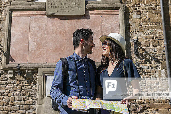 Couple with map looking at each other during sunny day
