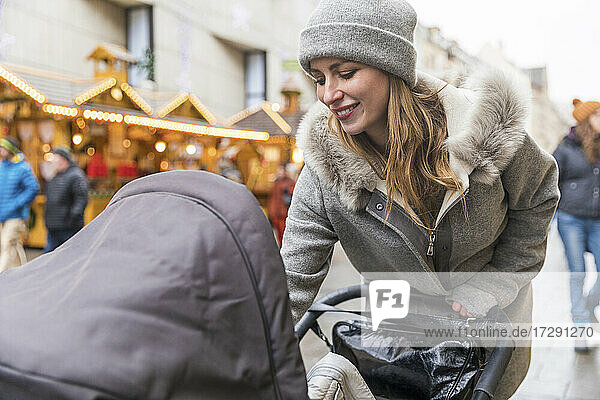 Smiling woman with baby carriage in city