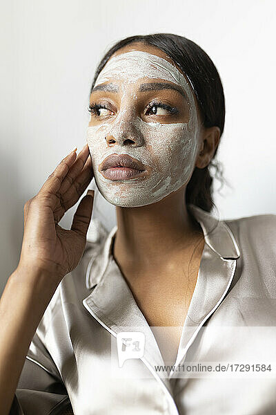 Woman looking away while touching face with beauty mask at home