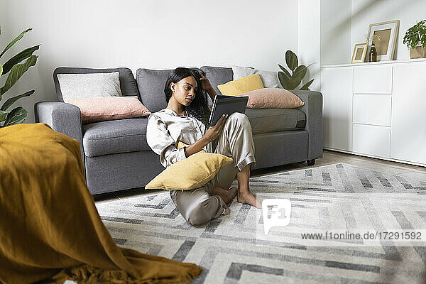 Young woman using digital tablet in living room at home