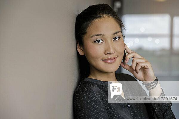 Lächelnde junge Frau  die im Büro mit einem Smartphone spricht