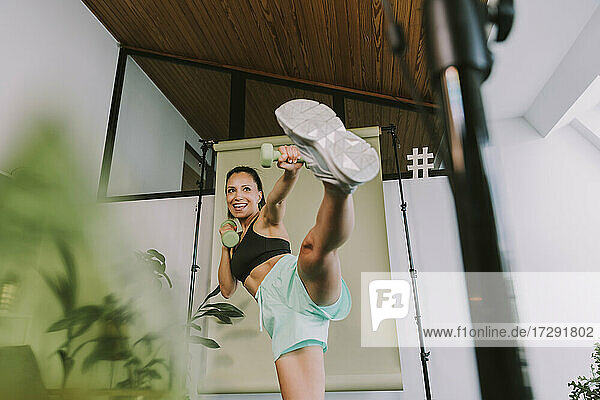 Female fitness instructor teaching high kicks while vlogging at home