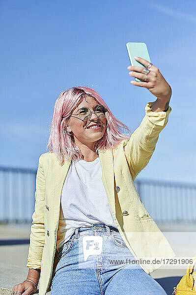 Pink haired woman taking selfie through mobile phone at promenade